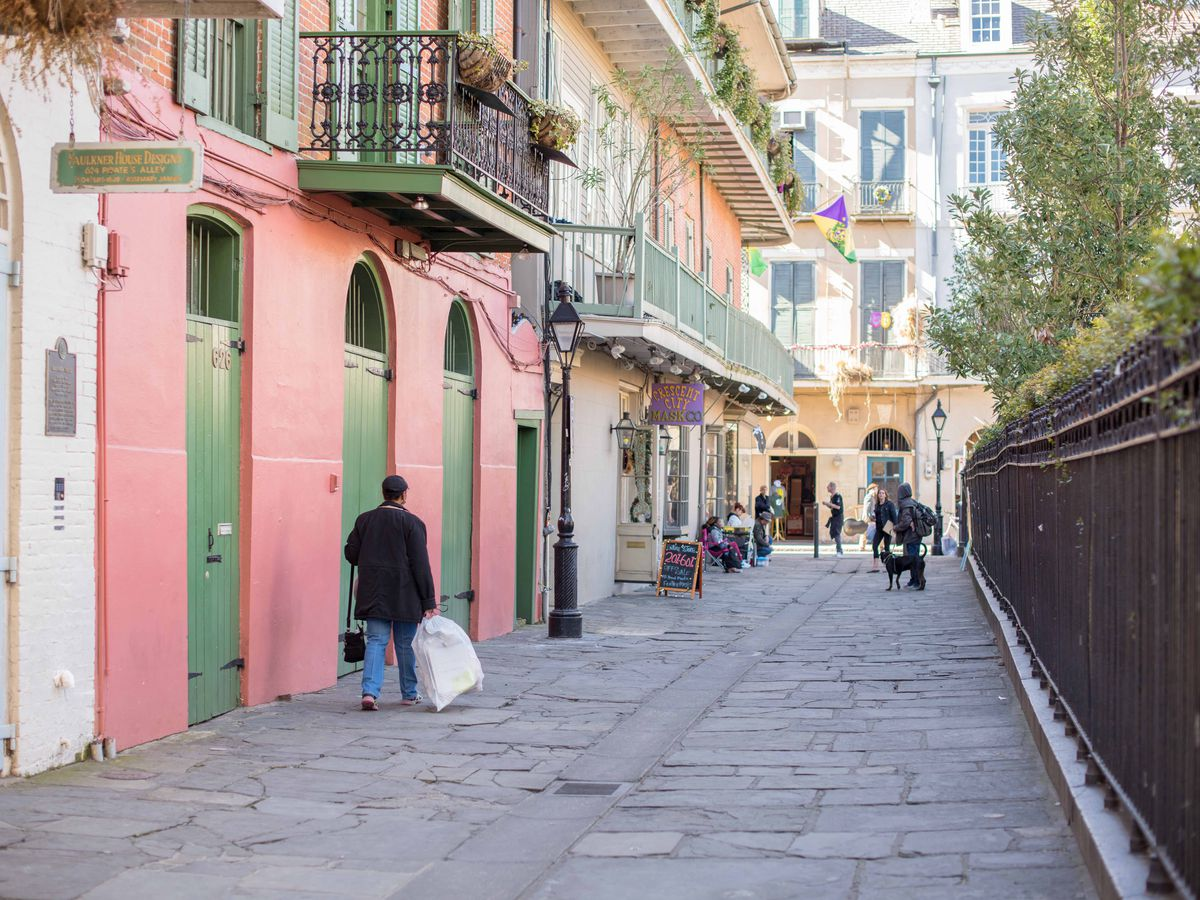 Pirate's Alley in New Orleans. There are a row of colorful houses with balconies.