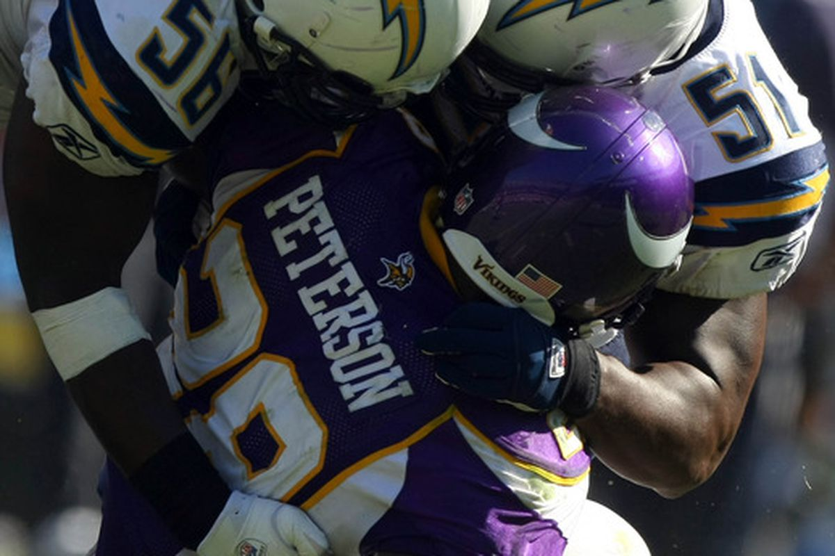 Adrian Peterson #28 of the Minnesota Vikings is tackled by Donald Butler #56 and Takeo Spikes #51 of the San Diego Chargers. (Photo by Donald Miralle/Getty Images)