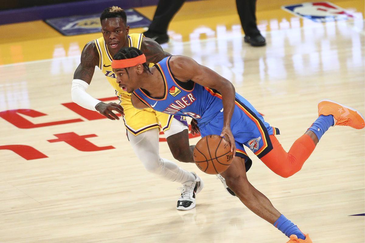 Shai Gilgeous-Alexander of the Oklahoma City Thunder moves the ball defended by Dennis Schroder of the Los Angeles Lakers at Staples Center on February 08, 2021 in Los Angeles, California.
