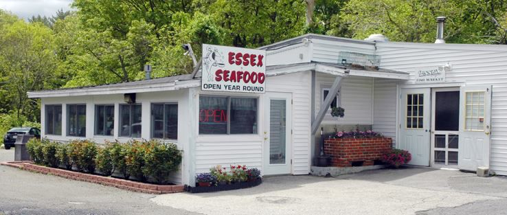 Exterior of a small white restaurant with signage reading Essex Seafood in bold red print