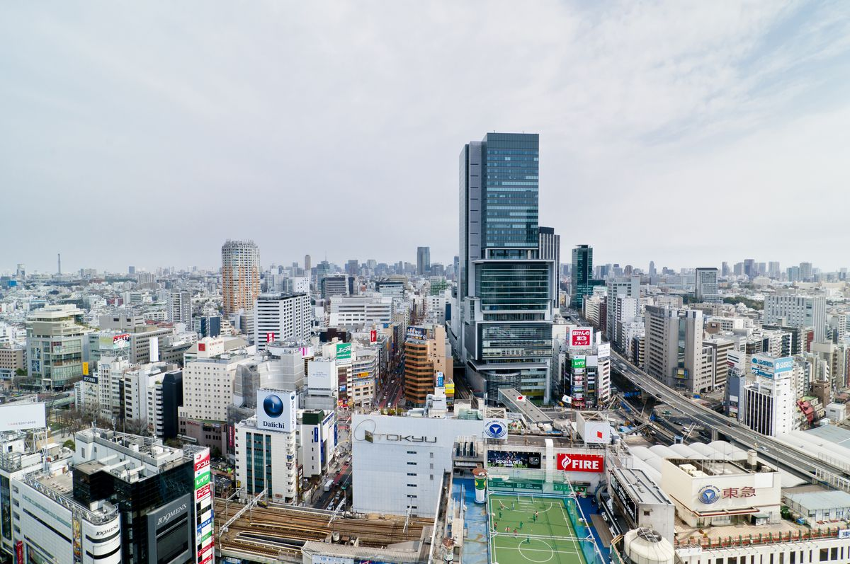 An aerial view of Tokyo. On one of the rooftops is a soccer stadium.