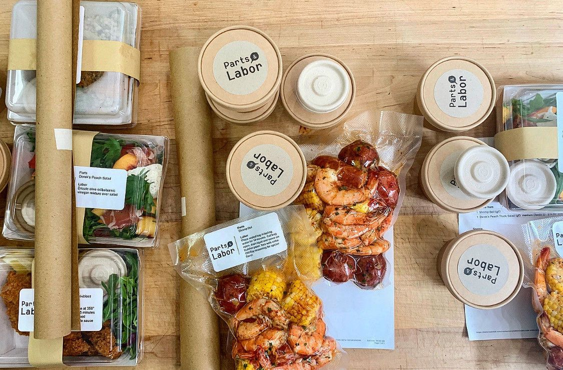 Various takeout containers of peach salad and shrimp boil