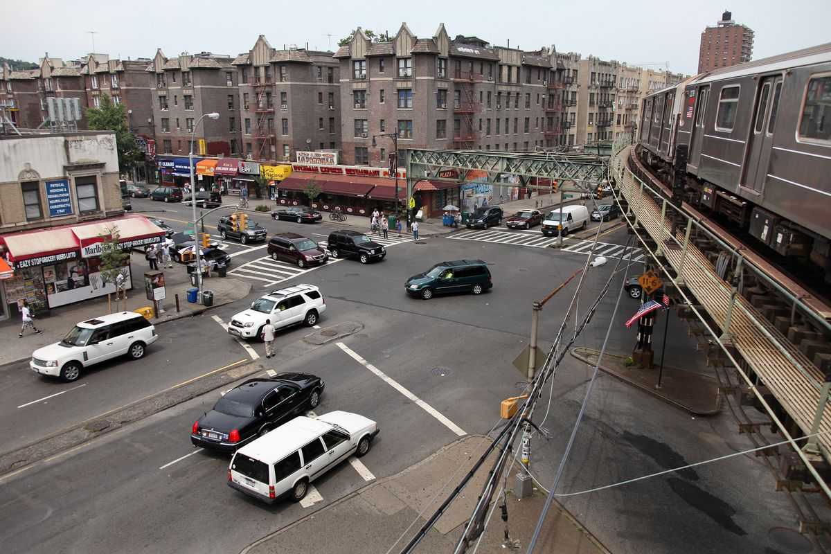 A busy intersection in Inwood, Manhattan is shown with cars zipping through. A train passes on the above ground subway over the intersection. A row of apartment buildings are in the background.