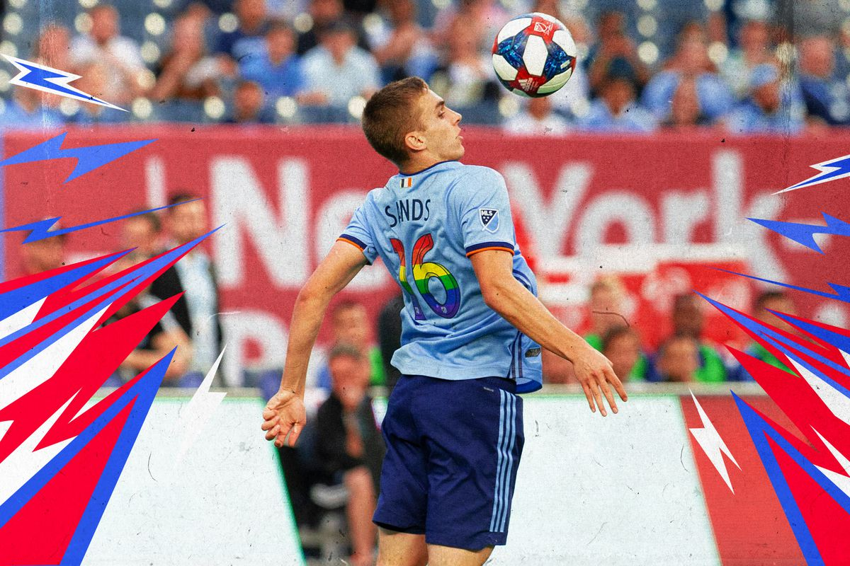 NYCFC's James Sands leaping to chest a soccer ball during a match.