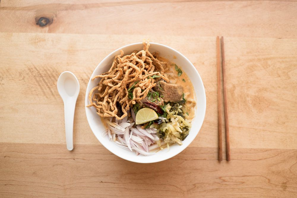 Overhead view of a white bowl full of a yellow curry with crispy noodles, preserved greens, a lime wedge, and red onion slices. It sits on a light wooden table with a spoon and chopsticks next to it.