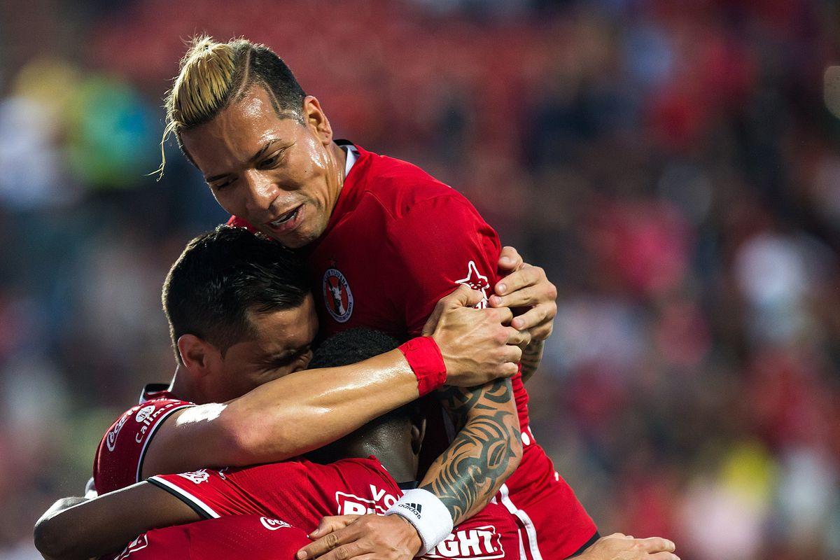 Xolos players celebrate a goal by Gabriel Hauche against Pumas