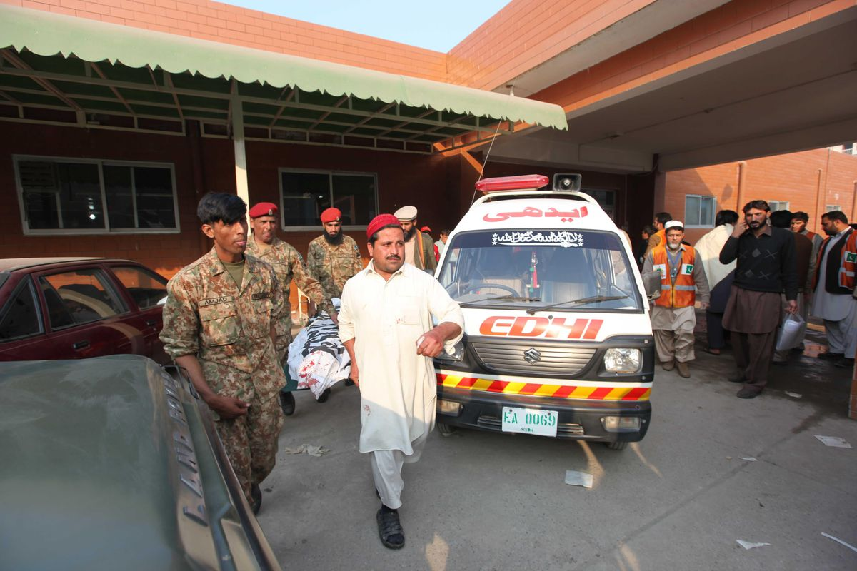 Pakistani soldiers carry a shooting victim's body out of the school after the massacre