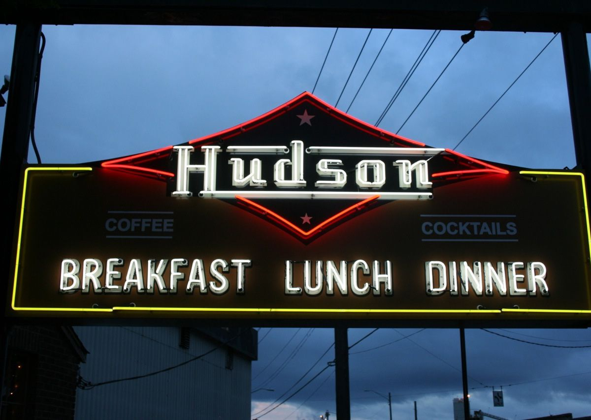 """The sign outside Hudson with the restaurant's name in white lettering, and the words """"breakfast,"""" """"lunch,"""" and """"dinner"""" below."""