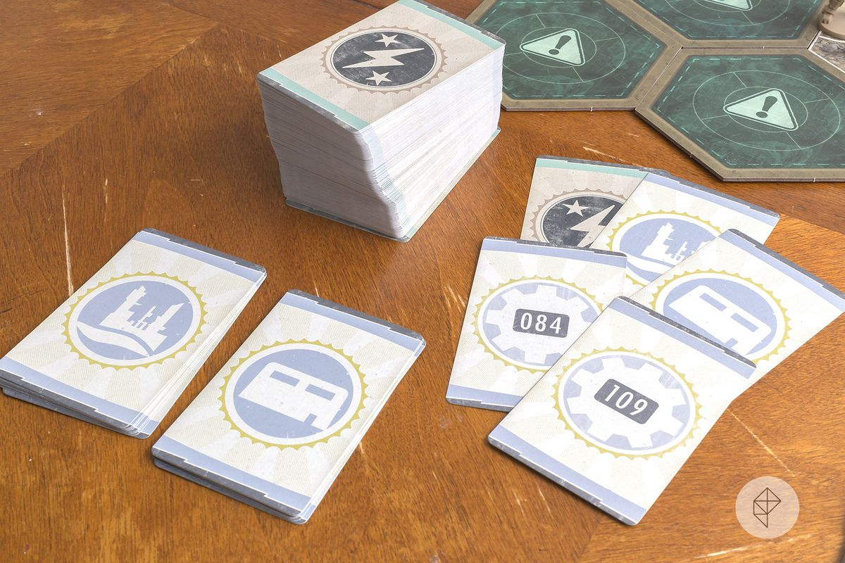 The more than 150 quest and encounter cards packaged in the game. All feature iconography from the classic franchise, including the geared vault door.