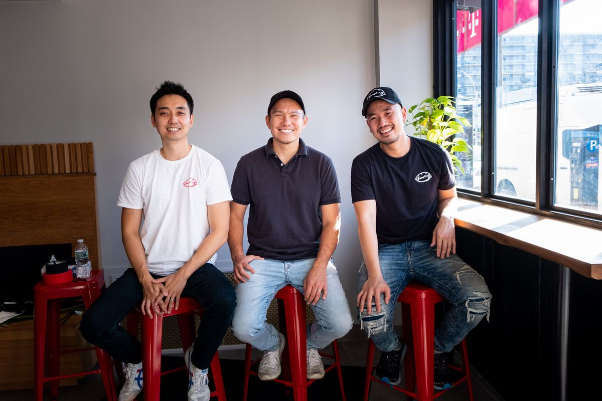 Three men pose for a photograph sitting on red stools inside a restaurant