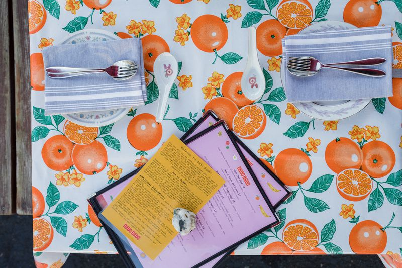 A table set with plates and silverware and menus on an oilcloth tablecloth