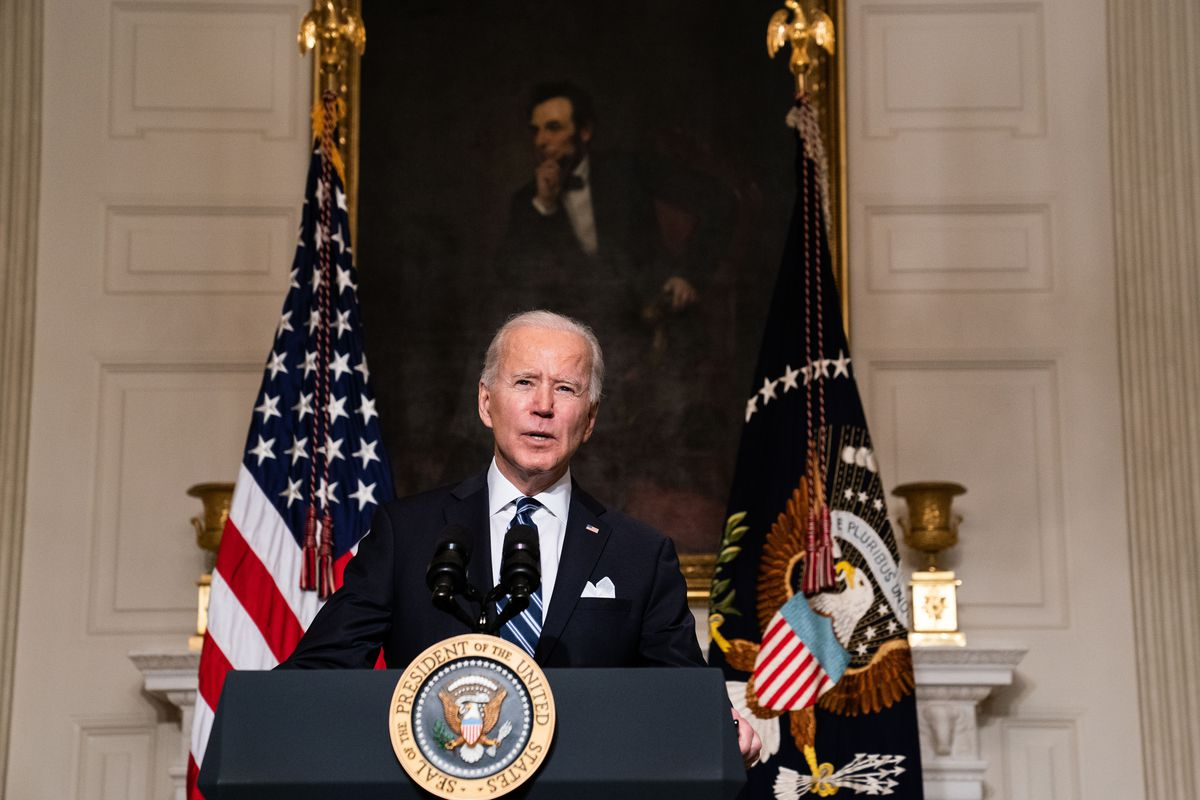 President Biden speaking from behind a lectern in front of a painting of Abraham Lincoln in the State Dining Room of the White House .