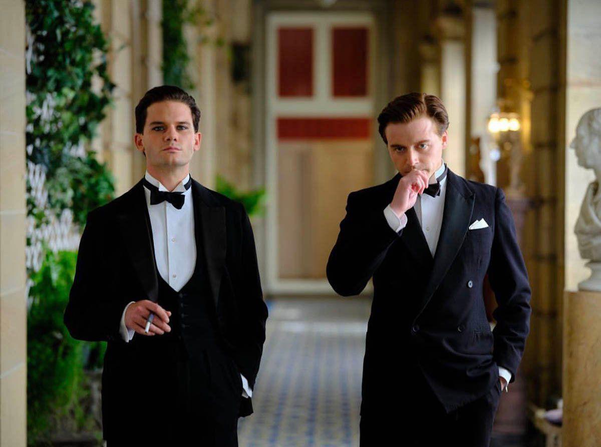 Two men in tuxedos smoke.