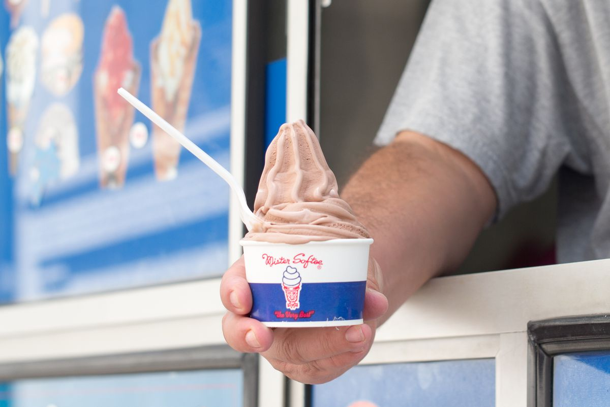 A man holds a cup of chocolate soft serve in a Mister Softee cup with a spoon in it.