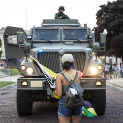 Officers with the Kenosha County Sheriff's Department approach in an armored vehicle as protesters peacefully gather at Civic Center Park on the fourth day of civil unrest after police shot Jacob Blake, Wednesday evening, Aug. 26, 2020. The officers left a short time later without any skirmishes with the protesters.