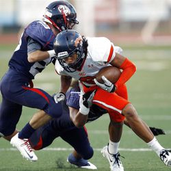 Woods Cross' #23 Chandler Judd, left, and teammate #7 Junior Vailolo work to bring down Mountain Crest's #6 Faimafili Laulu Pututau as they play Friday, Aug. 31, 2012.