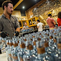 William Broder moves empty bottles from the staging area to the filling station during bottling day at Old 4th Distillery.