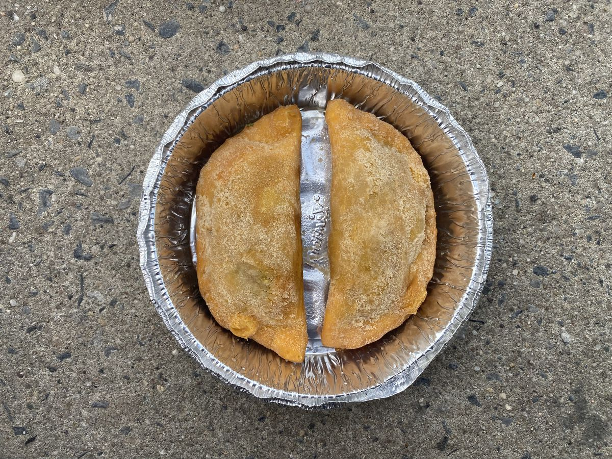 Two brown empanadas sit in a silver aluminum container with their flat sides facing each other