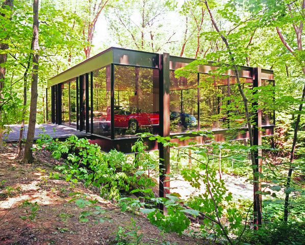 A glass garage over a ravine with trees. There is a red convertible parked inside.
