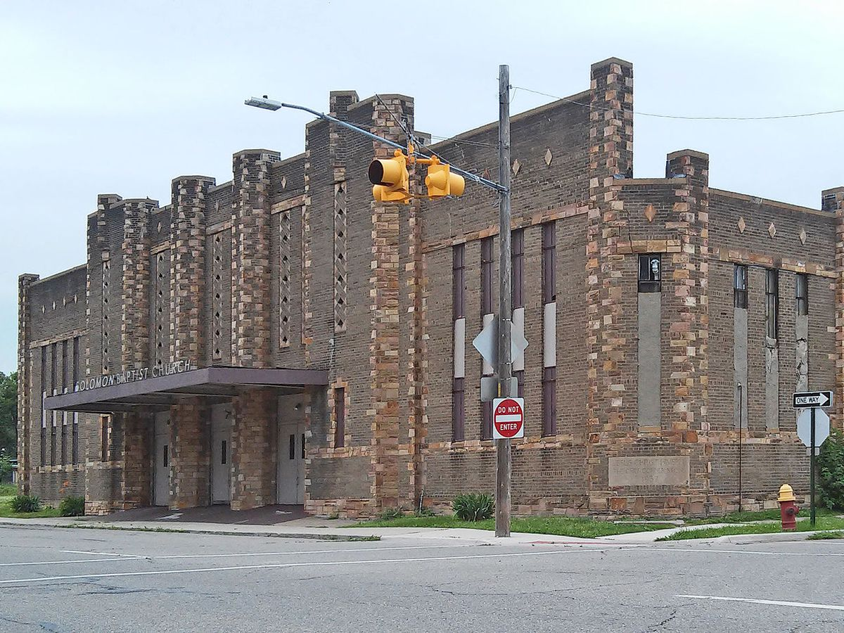 """Exterior of a brick building with stone columns and other stone details on the facade. Above an awning it says """"Solomon Baptist Church"""" in wobbly block letters."""
