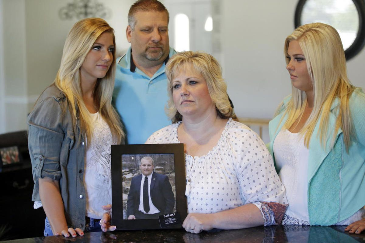 FILE - Laurie Holt holds a photograph of her son Josh Holt, while daughters Jenna, left, Katie, right, and husband Jason look on at her home Wednesday, July 13, 2016, in Riverton, Utah. U.S. Secretary of State John Kerry raised concerns during a meeting t