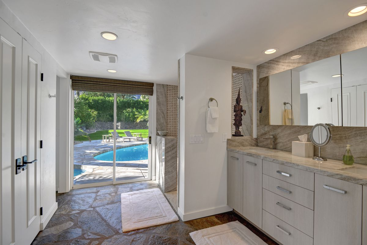 A master bathroom has gray cabinets and marble counters, a large mirror, stone floors, and a shower.