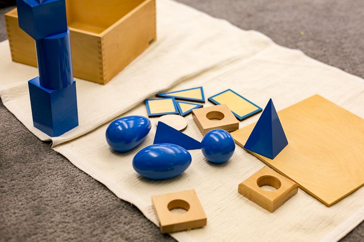 Montessori classrooms use specialized materials like wooden blocks to teach math and other concepts.