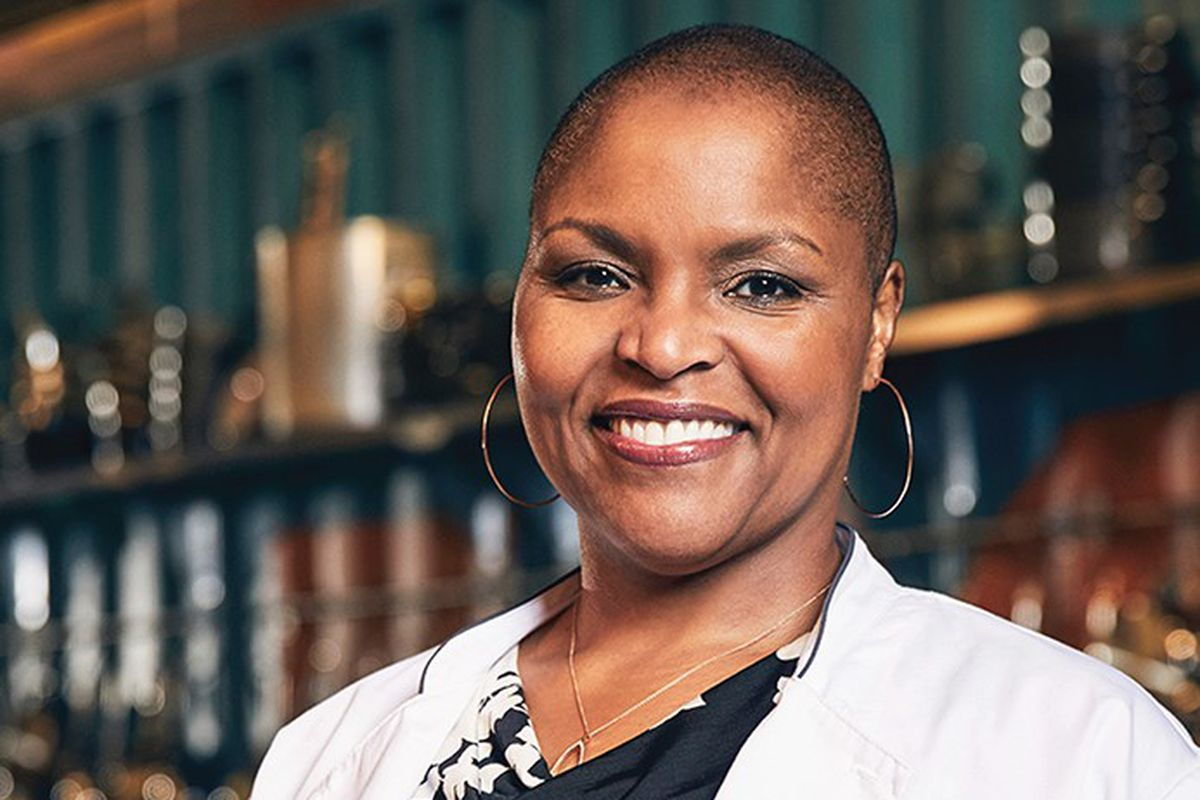 """A portrait of a woman with a shaved head and large hoop earrings. She is smiling and wearing a chef's coat that reads """"Top Chef"""" on the right side."""