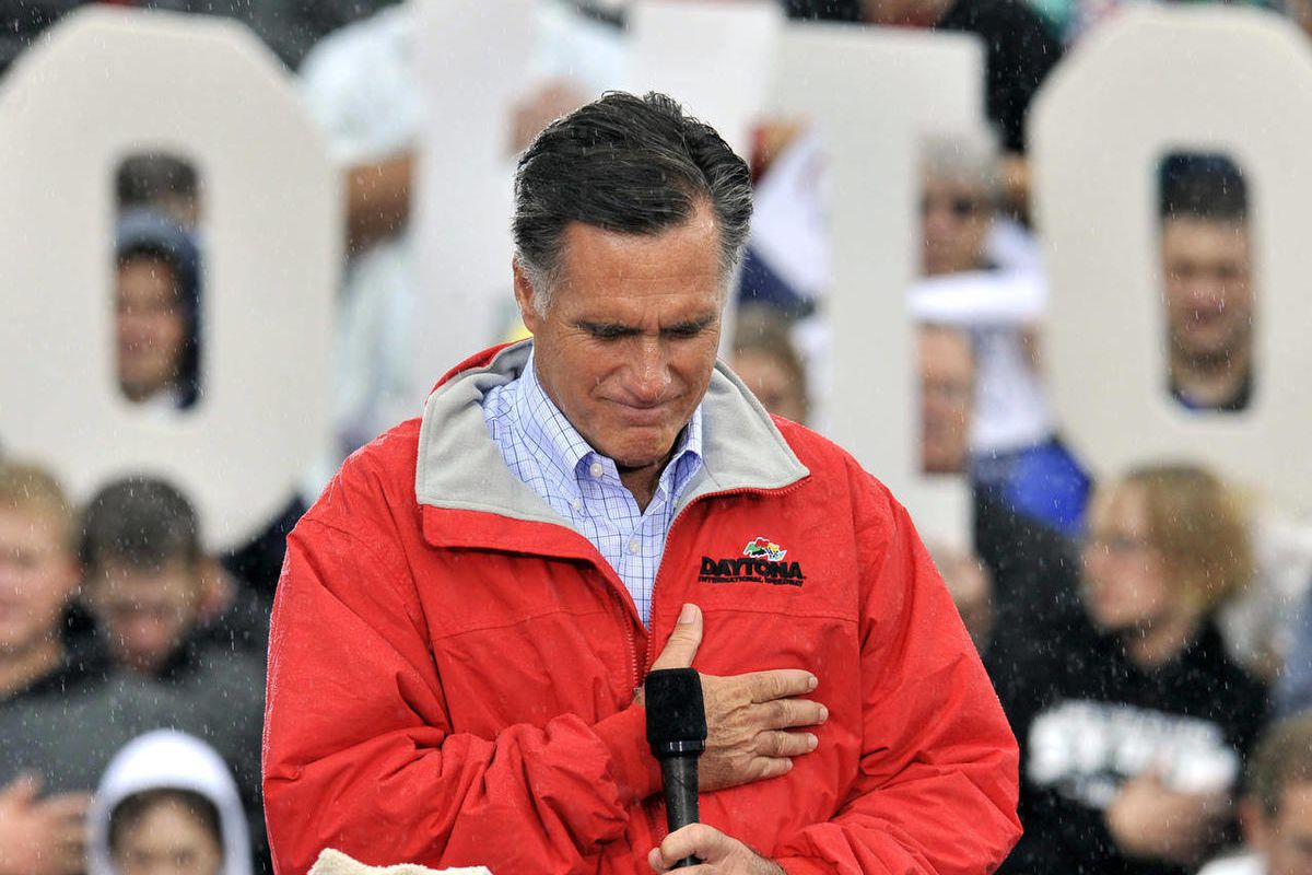 Republican presidential candidate, former Massachusetts Gov. Mitt Romney puts his hand on his heart during a moment of silence for the embassy officials killed in Libya, as he campaigns in the rain at Lake Erie College in Painesville, Ohio, Friday, Sept.
