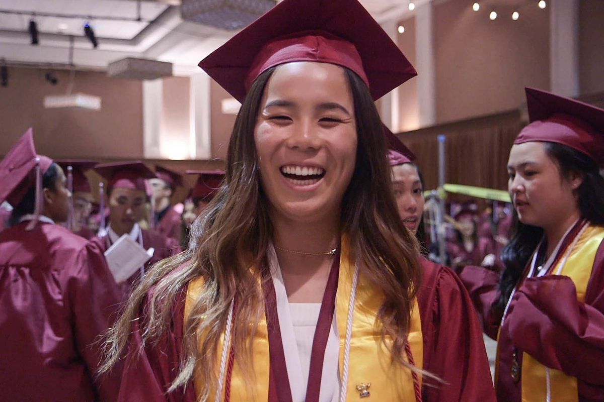 A teenager in a graduation cap and gown laughs at the camera.