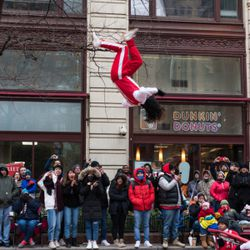 Spectators watch as a member of the Jesse White Tumblers flips high above State Street during the 85th Annual Thanksgiving Day Parade on November 22, 2018   Max Herman/For the Sun-Times