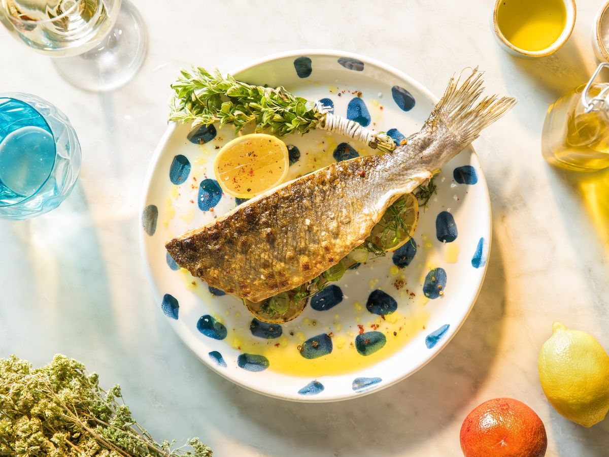 Grilled branzino on a white plate with blue spots