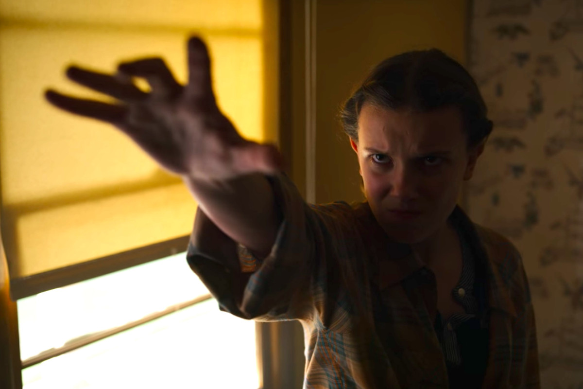 a young woman holds out her hand while performing telekinesis