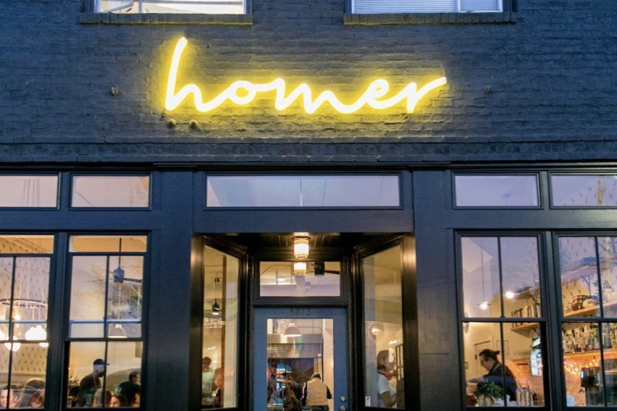 The storefront of Homer in Beacon Hill, Seattle, with a dark blue facade and the restaurant's name lit up out front in lowercase script