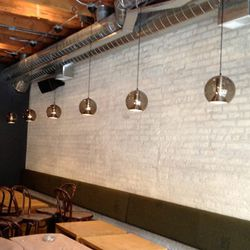 Mid-century modern hanging pendants and green wool Army blankets on the back of banquettes