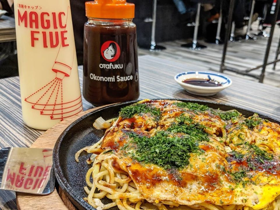 A skillet of onokomiyaki (eggs, noodles) with sauce and mayo bottles behind it
