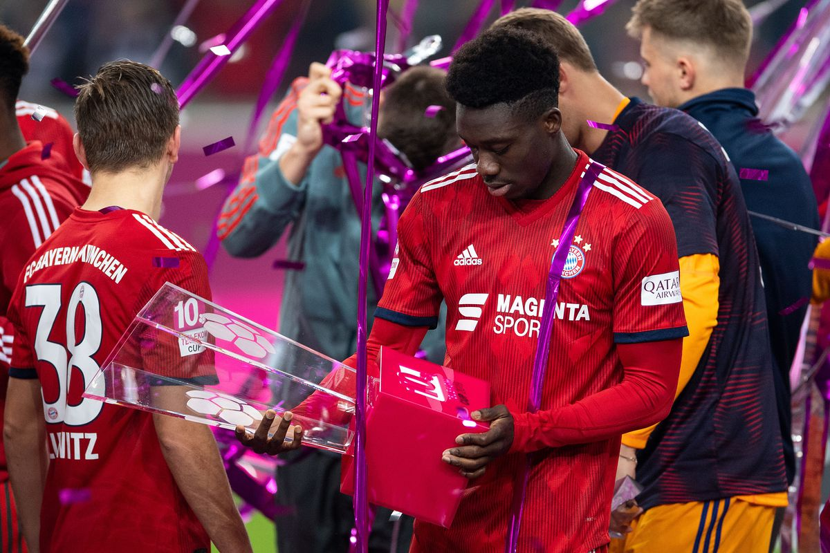 13 January 2019, North Rhine-Westphalia, Düsseldorf: Soccer: Bundesliga,10th Telekom Cup, Final, Bayern Munich - Borussia Mönchengladbach in the Merkur arena. Alphonso Davies from Canada looks at the cup after winning the final. The 18-year-old Canadian winter player made his debut at the short tournament.