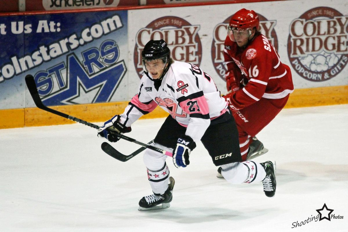 Michael Szmatula (right) battles for a loose puck in a game for the Dubuque Fighting Saints last season.