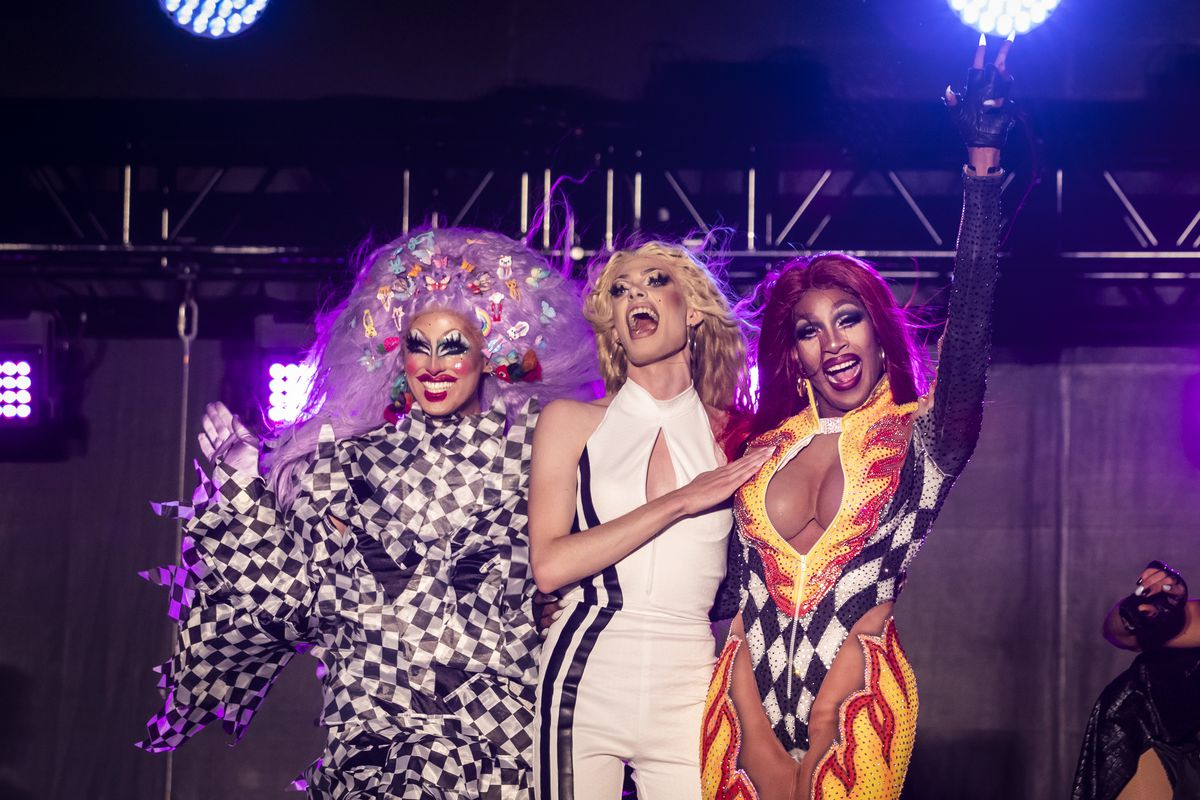 """Crystal Methyd (from left), Gigi Goode and Jaida Essence Hall wave to the crowd during Drive 'N Drag at Soldier Field. Hall won the 12th season of """"RuPaul's Drag Race""""; Methyd and Goode were runners-up."""