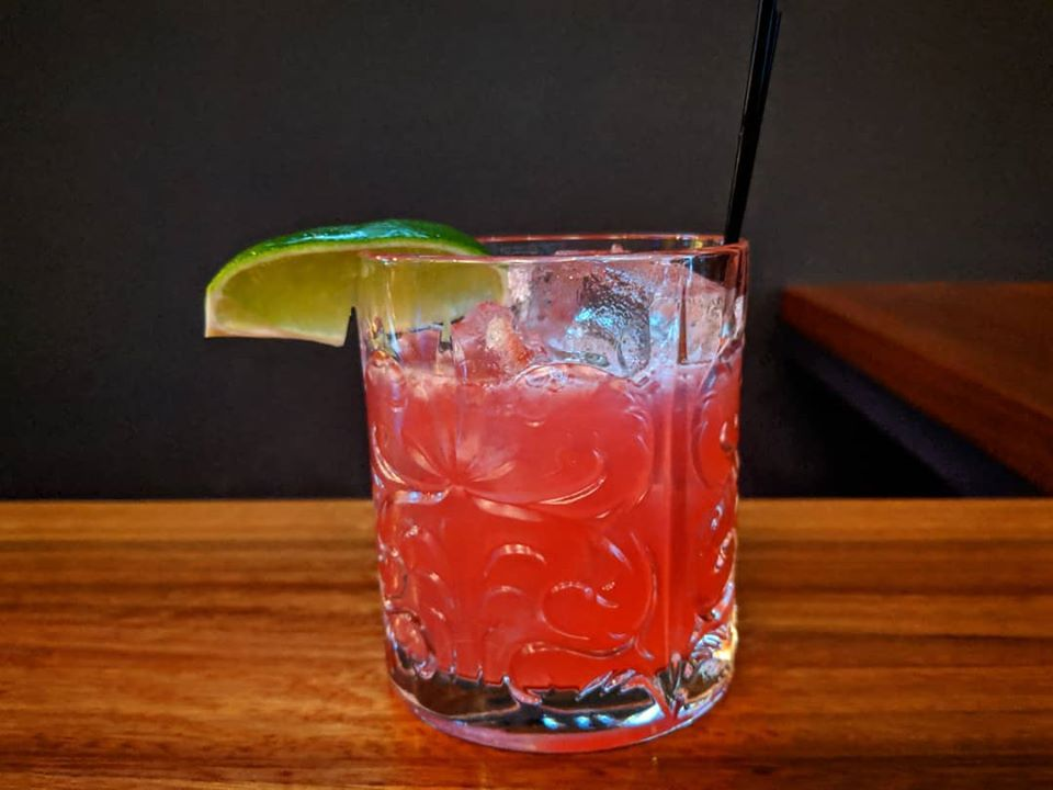 A bright pink cocktail in a short glass is garnished with a lime wedge. It sits on a light wooden bar in front of a black background.