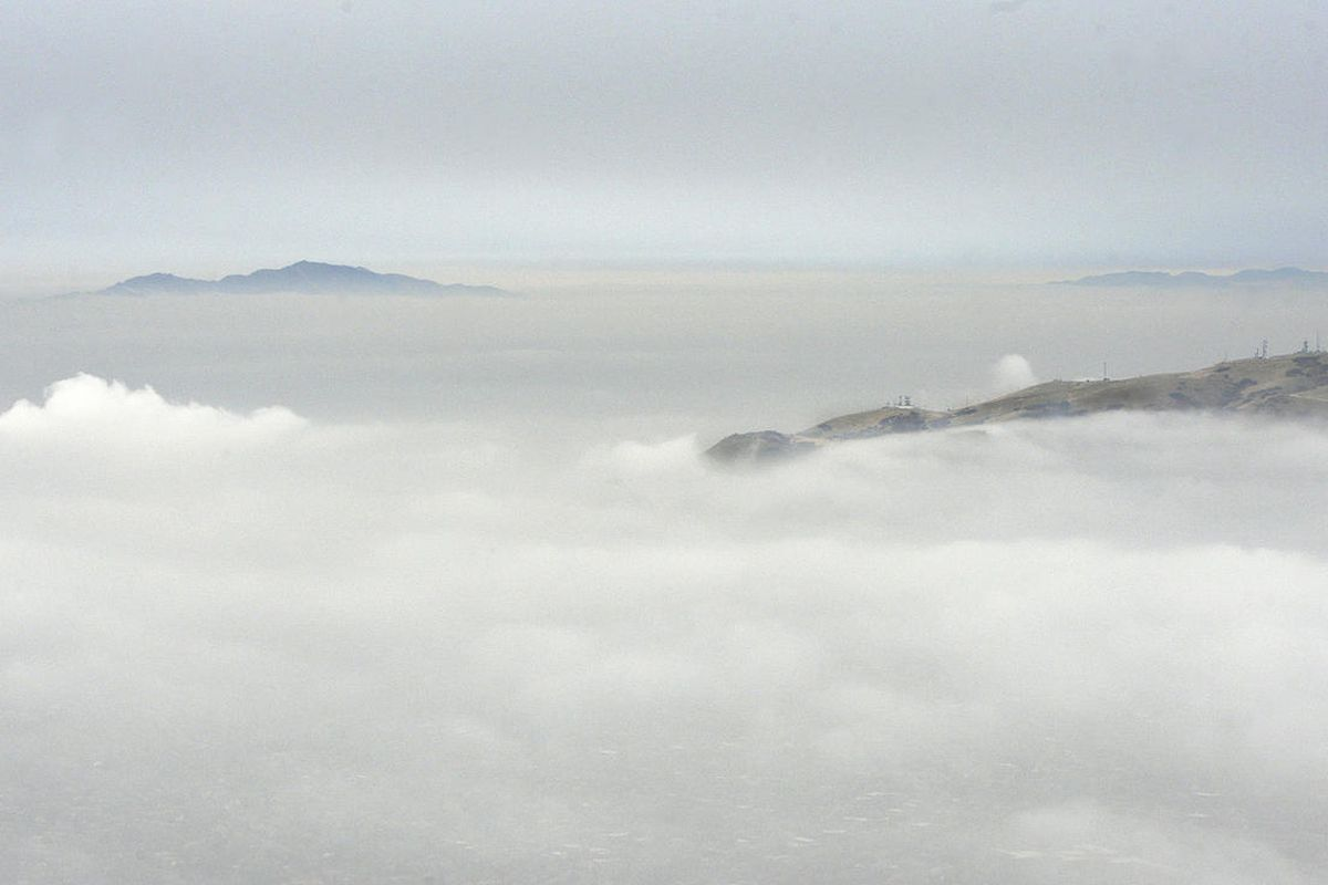 Part of Ensign Peak, at right foreground, pops up above the a layer of fog and smog as an inversion camps out over the Salt Lake Valley on Wednesday, Dec. 13, 2017. In the distance at left is Antelope Island.