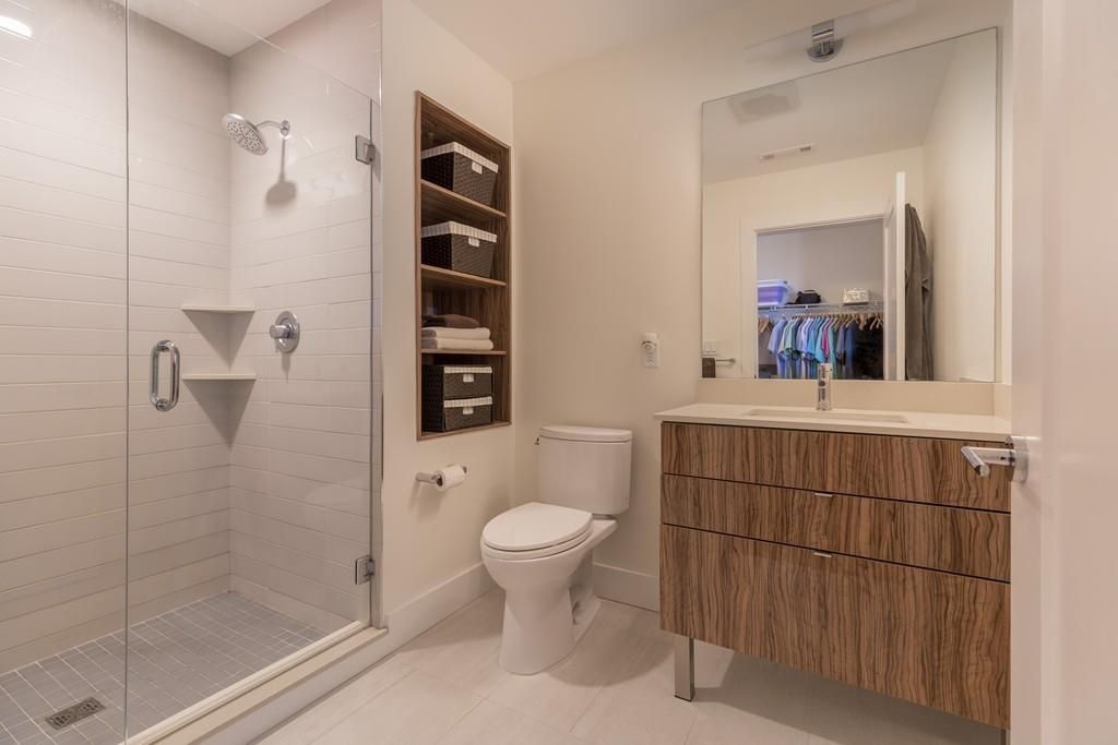 A bathroom with a glass-enclosed shower and a set of built-in shelves next to the shower.