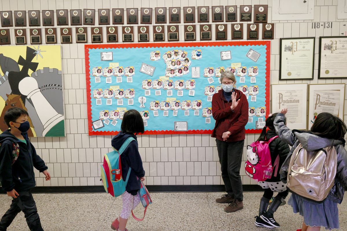 Four elementary school students with colorful backpacks walk by a middle-aged woman working as a paraprofessional and wave goodbye during school dismissal. The hallway is adorned with small awards and a sky blue board with student pictures on it.