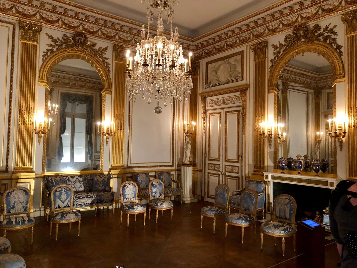 The interior of the Salon Dore at the Legion of Honor. There are multiple chairs, a chandelier, mirrors, and walls with inlaid design.