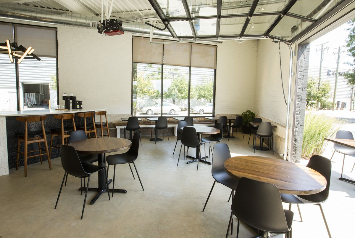 A cafe with round tables, coffee counters, open garage-door style windows.