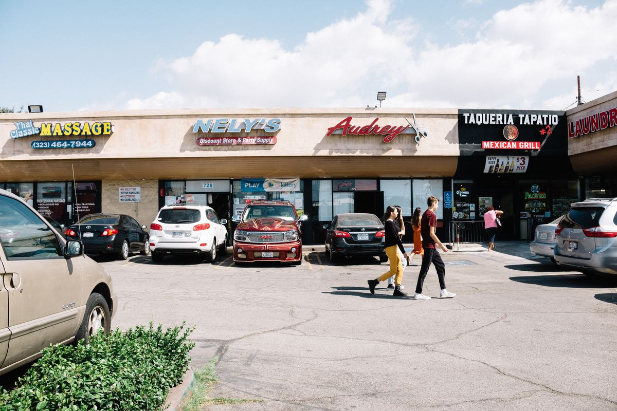 Young people walk through a parking lot in a small, beige stucco strip mall.