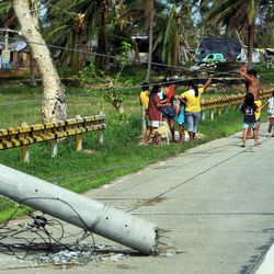 People hang onto downed power lines as they gather to talk in Tacloban, Friday, Nov. 22, 2013.