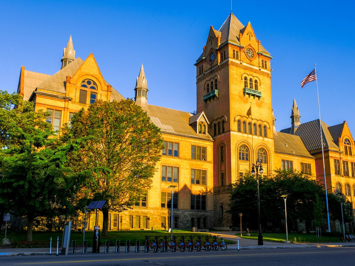 The exterior of Old Main at Wayne State University in Detroit. The building has a yellow facade with towers and a flagpole with a United States flag. There are trees and a courtyard in front of the building.