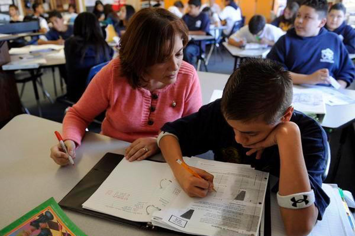 Middle school math teacher Eliana Moore, left, gives Armando Flynn, 13, some extra attention to help with a lesson in algebra.