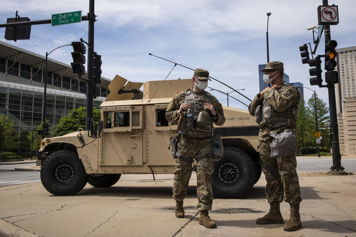 Members of the Illinois National Guard keep watch and direct traffic at their post outside McCormick Place near East 24th Place and South King Drive on Wednesday.